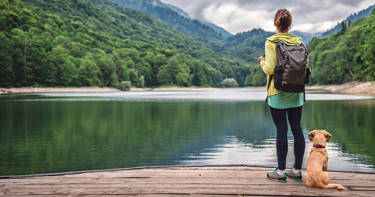 young woman standing on a dock with a dog. They are facing away from the camera looking out over some mountains. The woman is carrying a backpack. They look like they are about to set out on an adventure together.