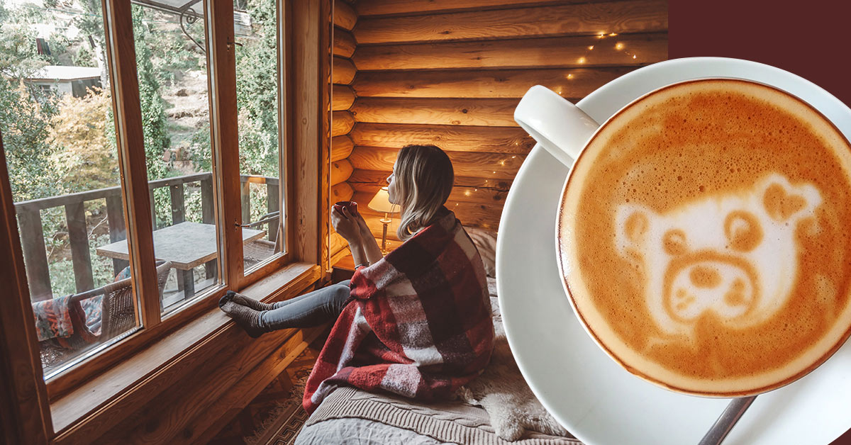 A woman with a big cup of coffee is looking out the window.